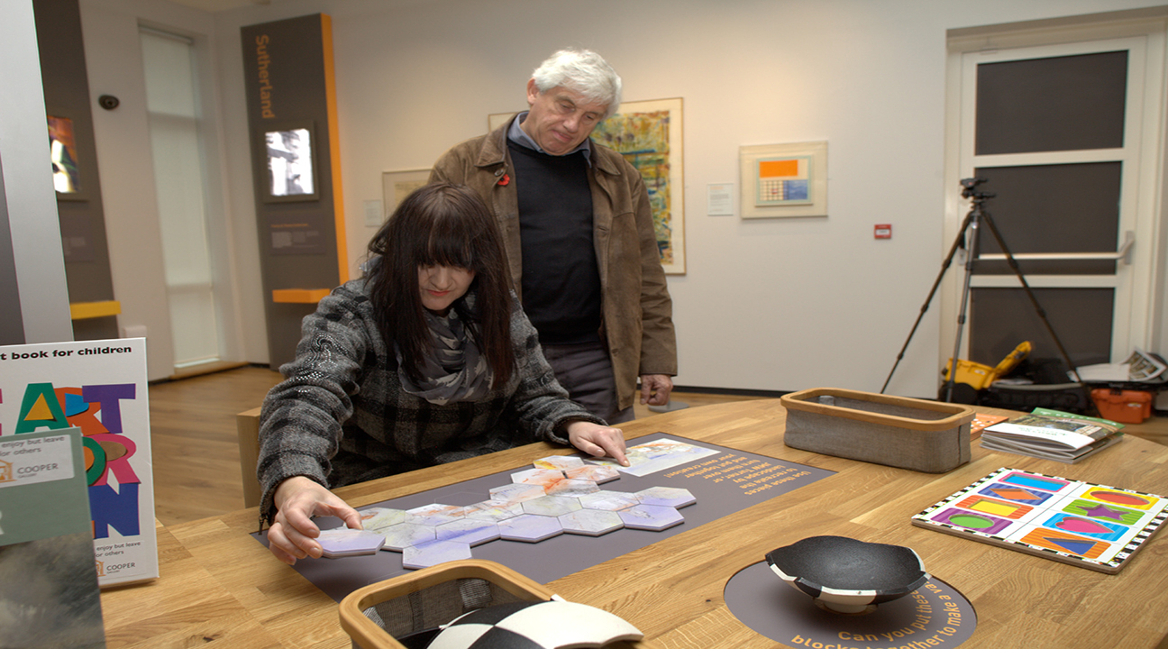 2 visitors inspecting an interactive feature at Cooper Art Gallery