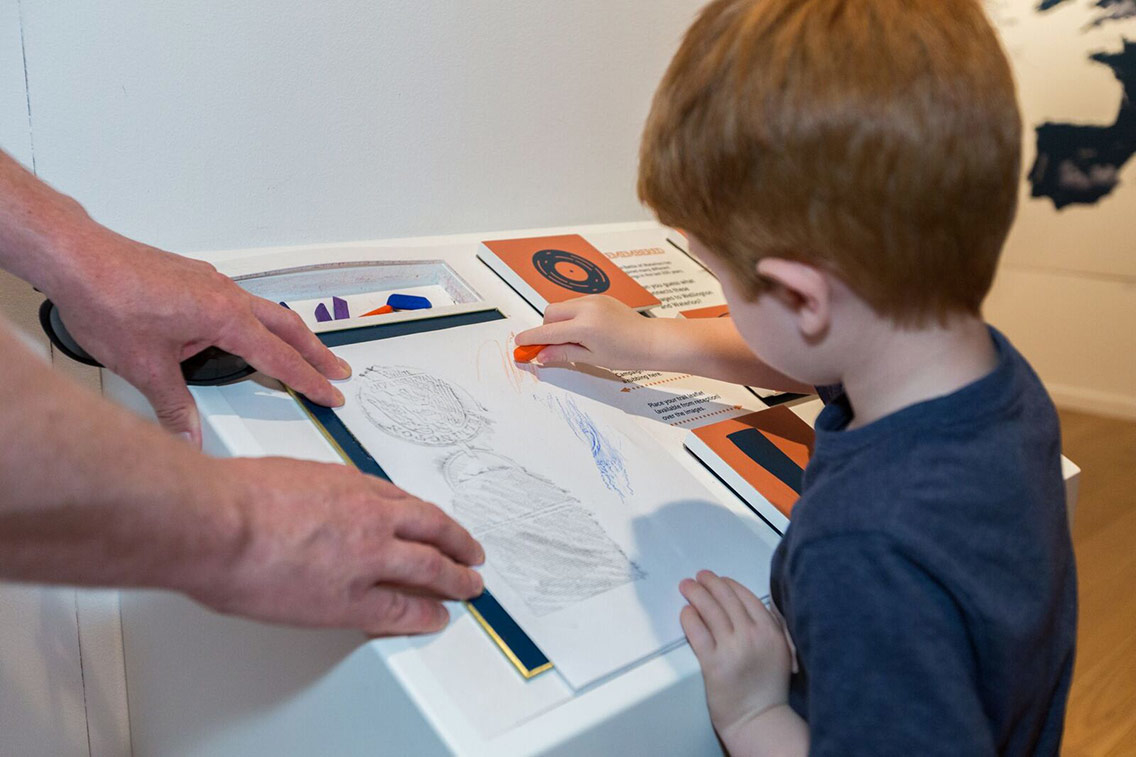 A child engages with interactive rubbing table