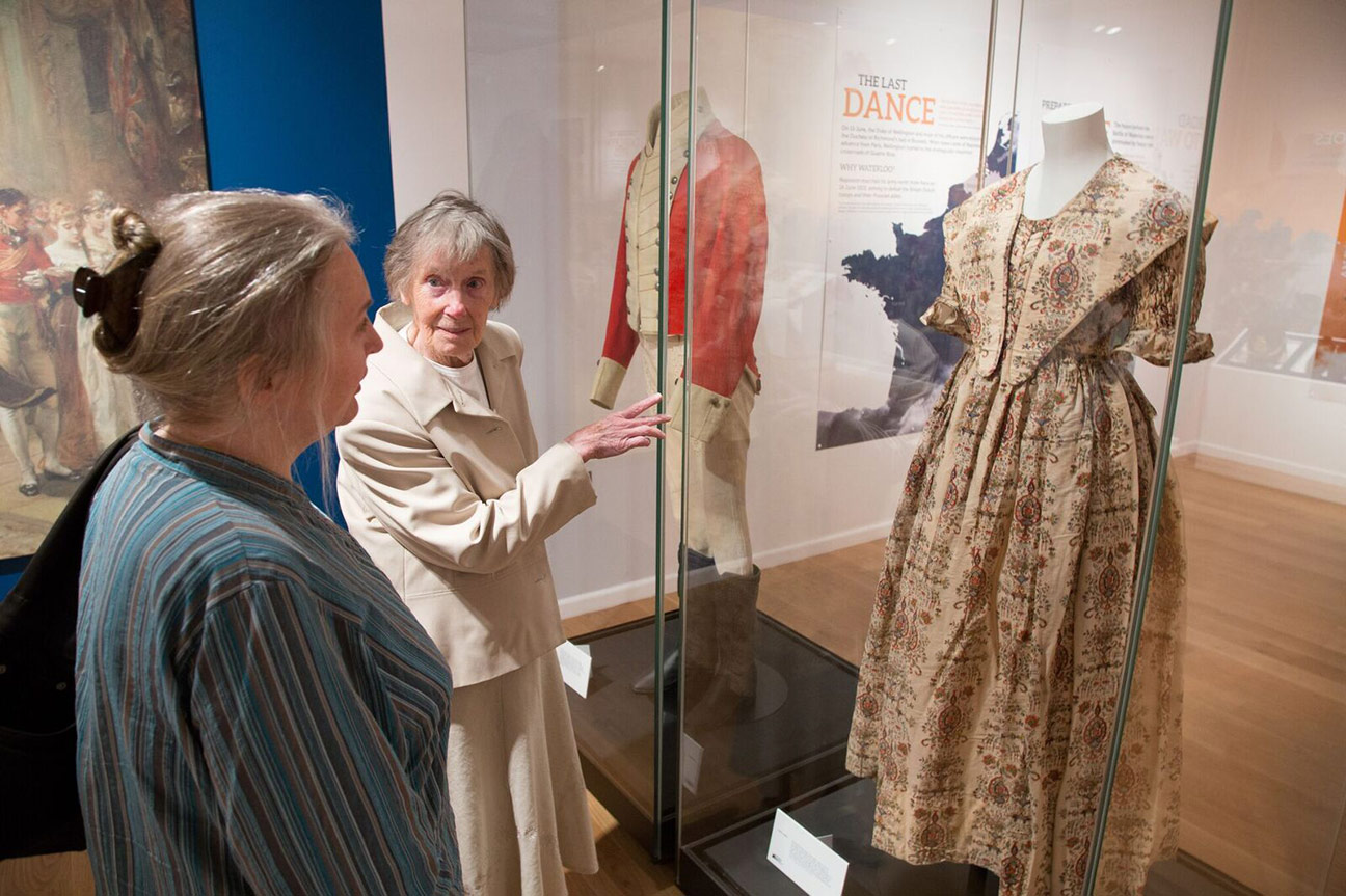 Museum visitors discussing period dress on display