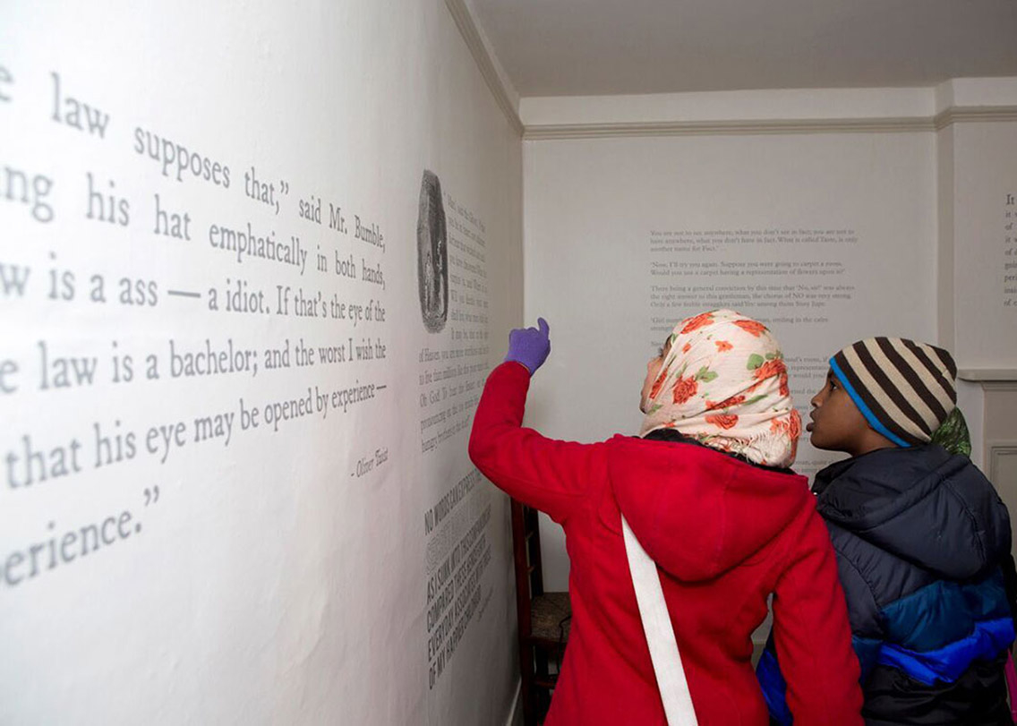 Visitors learning from the large information boards that adorn the walls of the Charles Dickens Museum