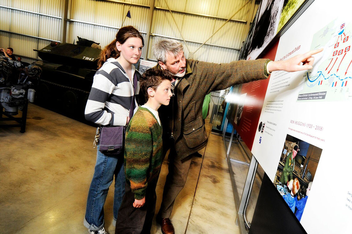 Family learning from the information boards on display at the Tank Museum, Dorset
