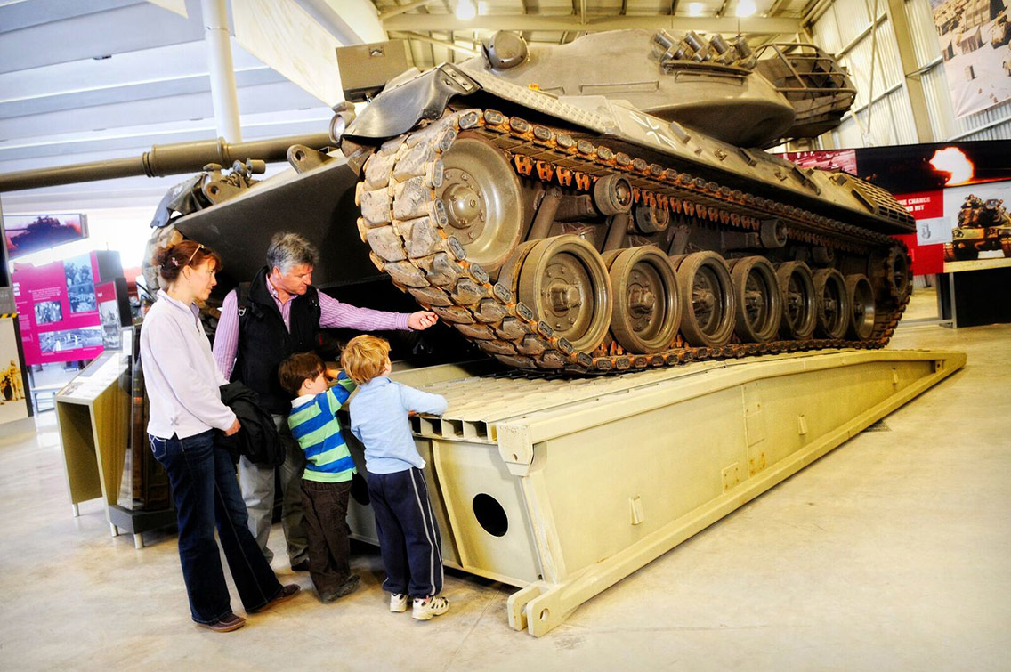 A member of staff talking to a couple of guests through the different components of a tank
